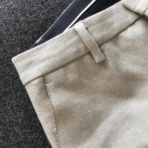 """Varetype: Chinos Størrelse: 32/32"""" Farve: Sand Oprindelig købspris: 1600 kr.  Chinos i 46%linen, 54% polyester. Stoffet er kraftigt og ligner en kraftig hør. Bukserne har kun været brugt få gange. Jeg har dog sat standen til """"god men brugt"""", da der Desværre er kommet en lille plet på ca 0,5 cm i diameter. Derudover er de desværre gået lidt op i syningen for neden. Dette kan jeg sende et billede af, hvis du er interesseret. Det kan sagtens sys i hånden. Pletten formoder jeg kan gå af i vask eller til rens - jeg har ikke forsøgt, da de bare har hængt i mit skab. Grundet disse ting har jeg sat prisen lavt ift oprindelig købspris.  Hvis du vil sparre fragten, kan jeg mødes og handle i København. Jeg bytter ikke:)"""