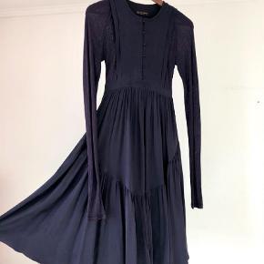 Varetype: Smukkeste silkekjole Farve: Blomme  Smuk smuk kjole fra Burberry med mange fine detaljer i lækker blød 100% silke. Mørk blommefarve. Skjult lynlås i siden og fine knapper ned over brystet. Bindebånd, hvor kjolen skærer under bryster. Masser af fylde i underdelen og underkjolen, som også er i 100% silke. Som ny - brugt én gang. Str. 42 (passer dk str. 36-38) Mp 2500kr