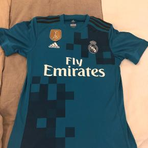 Sælger denne Real Madrid 3. trøje fra sæson 17/18 i størrelse small. Der er tryk med Luka Modric, som vandt Ballon d'Or efter denne sæson. Er i perfekt stand og er brugt 1-2 gange. Læg dog mærke til at FIFA World Champion logo'et på brystet er lidt løst forneden (se billedet). Trykket er perfekt og uden slidtage. Sælges udelukkende da den er for lille. Kan afhentes i Hellerup eller sendes med DAO.