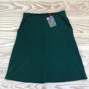 """Knælang A-formet nederdel med to lommer foran fra """"Who's That Girl"""". Mørkegrøn med sorte prikker."""