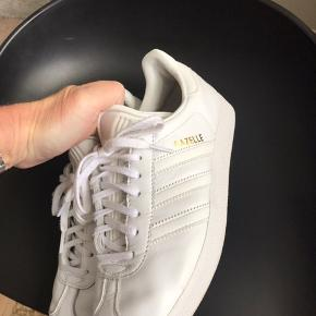 Adidas Gazelle i hvid med guld skrift. Brugt men i pæn stand. Nypris var 800. Dao er inkluderet i prisen.