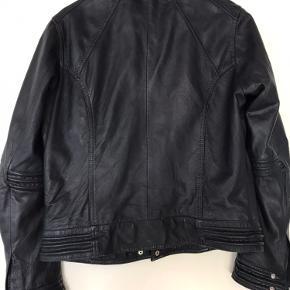 Lækker kort bikerjakke i navyblåt læder. Næsten ikke brugt. Med fine detaljer ved ærmer og i halsen. Med inderlomme og to lynlåslommer foran.