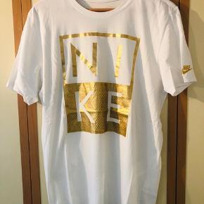 Hvid T-shirt med stort tyk for i guld fra Nike sælges pga pladsmangel. T-shirtsene fremstår i perfekt tilstand, uden nogen form for pletter, huller el anden form for slitage.  Kom og giv et fair bud