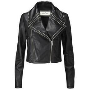 Varetype: Skindjakke Farve: Sort Oprindelig købspris: 4999 kr.  Super cool jakke i det blødeste skind. Flotte detaljer med nitter. Helforet. Længde 45 cm. Bryst 90 cm. Liv 80 cm. Måler omkring skuldrene ca. 104 cm. Aldrig brugt. Ej bytte.