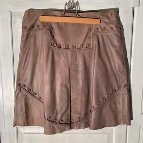 Læder nederdel med nitter i lysebrun  Lidt pletter i linning men ellers fin stand  Nypris: 2500kr