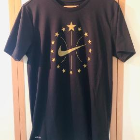 Frisk T-shirt med stort print for samt lille print i nakken fra Nike sælges da den aldrig bliver brugt. Har vært i brug 4-5 gange siden den blev købt, og fremstår i perfekt stand, uden nogen former for huller, pletter el anden slitage.  Kom med et fair bud