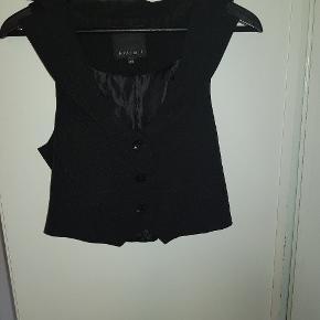 Kort sort vest. Fed over en hvid eller grå T-shirt og med jeans til. Brugt en enkelt gang.