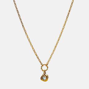 DORITH NECKLACE  Denne halskæde har en lille facetteret og glimtende Labradorit siddende i et vedhæng med smeltet tekstur. Kæden består af en smal Figaros kæde med en lille snoet øsken, hvori den lille amulet hænger.  Pris: 450 DKK Længde: 45 cm  Materiale: Sterlingsølv (925), belagt med 18 karat guld, labradorit.