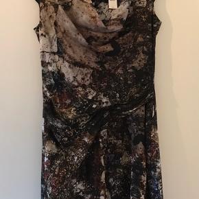 Smuk og velsiddende silkekjole med flotte draperinger  Købspris 485 US $ (3.150 dk.kr.) Str. US 6, passer en str. S Brugt 1 gang.  Farver; Sort, brun, grå, grøn, hvid Har en plet ved brystet indvendigt på underkjolen. Den var der ved køb af kjolen, så ved ikke hvad den er kommet af.