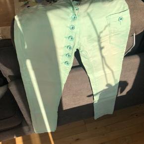 Fede mintgrønne stumpebukser med masser af stretch og skrå knaplukning, der går ned på låret.   Mærket er Onado.   Farven på det første billede, er farven på bukserne.   Køber betaler evt porto. Jeg sender med Dao.