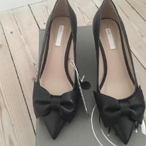 Læder pumps med sløjlfe og kitten heels. Aldrig brugt.   Pumps Farve: Sort Oprindelig købspris: 499 kr.