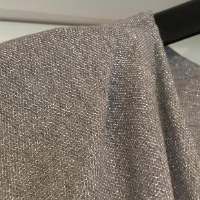 Fin blød top med sølvtråde  47 % polyester 27% lurex 23 % polyester 3 % elestan Brystmål  51 cm x 2 Længde 58 cm  Top Farve: Sølv, Sølvgrå