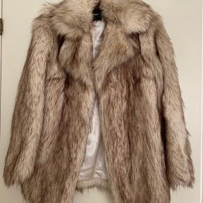Smuk, varm oversize faux fur i lyse nuancer med satinfor. Brugt få gange. Størrelse 36/S. Lukkes med hægter.   Kan afhentes i Middelfart eller København efter aftale. Kan også sendes, såfremt køber betaler forsendelse.