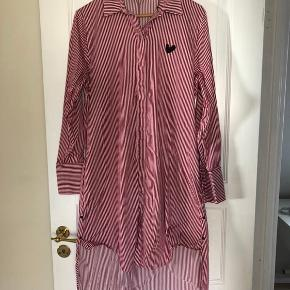 Stribet skjortekjole af Rika Studios. Den har skjulte knapper og to lommer.  Længde Foran 90cm Bagpå 110cm