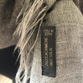 Tørklædet er grå/brunt. Brunt på midten, som fader lidt ud og bliver mere svagt gråligt. Blødt som smør. Cashmere og silke.