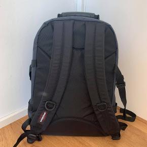 """Mørkeblå Eastpak taske. Mål: 45x30x20. Der er et stort rum med et rum indeni til en 15"""" pc. Udover det er der et godt rum til fx. madpakker og et lidt mindre rum til bl.a. penalhus. Tasken har været i brug 3 måneder og ingen store mærker eller lign. Er en unisex taske. Skriv for flere billeder."""