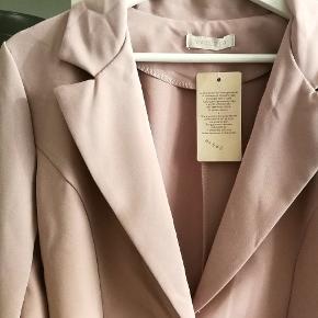 Helt ny let blazer i en flot, sart lyserød farve med stor guldfarvet knap.  Blazeren sidder lidt tæt i taljen og har lidt peplum-form, som gør taljen flot.  Ingen lommer eller skulderpuder.  95 % polyester, 5 % elastan.