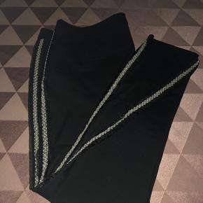 Meget lækre bukser med smarte på syet perler ned langs siden. Sorte i str. 46  Helt nye og aldrig brugt.