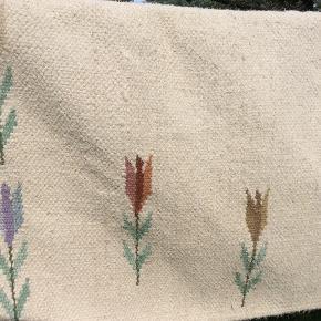 Smukkeste kelim-tæppe, brugt men stadig i god stand, kan vaskes i stor industrivaskemaskine på kold uldprogram, eller renses. Tæppet er i fin og pæn stand og ikke meget beskidt, er luftet i solen. Skønneste farver med blomster-vævning. Kragftigt varmt skønt uld-tæppe. Lidt slid på midten af tæppet se foto, ses ikke når det ligger på gulv, og tæppet er vendbar. Mål er ca. da jeg har målt det mens det hænger på tørresnor, ca. 200*135 cm. Det er tungt så porto vil være mellem 44-58 kr. dao. Mp 300.