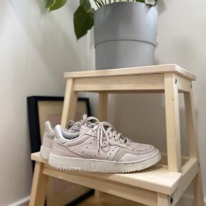 Rosefarvet Adidas Supercourt. Sindssygt behagelig sneaker! ikke brugt ret meget, da jeg også har dem i hvid. Str. 38 2/3 - er selv 39 og passer dem fint, da de er en anelse store i størrelsen.