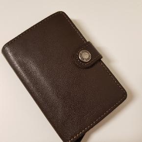 SECRID Miniwallet  Virkelig lækker læder pung fra Secrid Miniwallet, der aldrig har været brugt. Den har dog været pakket ud.   Størrelse:65 x 102 x 21 mm  Plads til: - 4 prægede eller 6flade kort  - 4 ekstra kort - Pengesedler - Visitkort - Kvitteringer  Ny pris 450 kr Kom gerne med bud