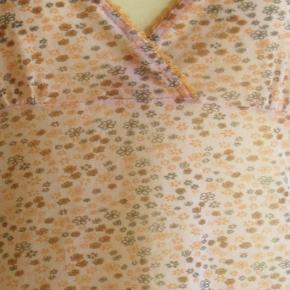 Sød top i let gennemsigtigt mesh-materiale. Meget strækbar. Farve: råhvid bund m blomster  Brystvidde når den ligger fladt på bordet: 84 cm + meget stræk Længden målt fra ærmegab og ned: 42 cm  Ingen byt, og prisen er fast