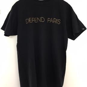 Defend Paris tee 'Defend Paris' er broderet med guld tråd.  Str. Large Brugt 2-3 gange.   Har massere af mærkevare til salg, så tag et kig, det er gratis.