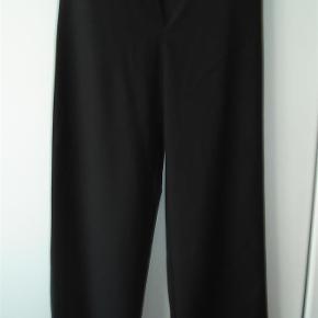 Varetype: Lækre bukser med vidde i benene og i lækkert stof Farve: Sort  Superlækre, sorte bukser i størrelse 42 fra Carla du Nord med vidde i benene og smart lynlåsdetalje. Lynlåsen er skråtstillet og linningen lukkes med 2 knapper ala sømandsbukser. I linningen sidder et smalt bånd, der bindes bagpå. Lavtsiddende talje, der måler 90 cm. Benlængden er på indersiden målt til 82 cm. Fodvidden er 31 (gange 2). 53% polyester 43% uld 4% lycra. Aldrig brugt. BYTTER IKKE!