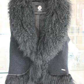 Kulsort strikket pelsvest med tibetansk lam. Glat sort foring. Beklager billede kvaliteten.