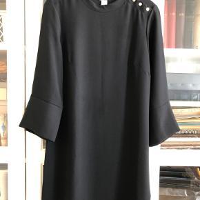 Sort tunika/kort kjole med små guldknapper. Glat pænt stof (virker krølfrit) 3/4 ærmer med slids og lille guldknap. Aldrig brugt. 100% polyester. Længde fra nakke til nederste kant 86 cm.