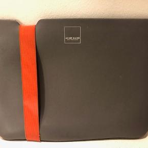 """Cover, t. iPad, MacBook etc  Lækkert designet cover, der fx passer til en MacBook Air.  Herlig farvekombination - grå & orange. Orange stikninger langs kanten gi'r den et ekstra pift - se billeder.  Mærke: Acme Farve: Grå med orange """"bånd"""" og orange stikninger Størrelse: 28.5 x 22 cm  Nypris: 299 kr  Brugt. Fremstår pænt.  Check størrelsen på din iPad, MacBook med de opgivne mål."""