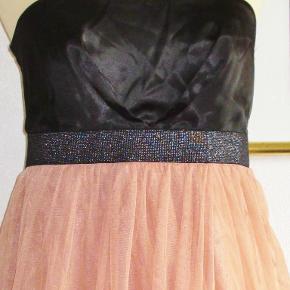 Farve: Sort + nude/rosa  Smuk kjole med sort satin-top og med drapperet tyl-nederdel. Elastikbælte i sort og sølv. Kjolen har anti-skrid kant foroven, så den bliver hvor den skal.  Brystvidde: 47 cm x 2 Livvidde: 40 cm x 2 Længde målt i siden -altså under armen: 69 cm.  Ingen byt, og prisen er fast