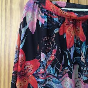 Nederdel med flot blomstermønster i mesh-stof. Den har for og et bindebånd, som mest har en dekorativ funktion.  Bytter ikke.