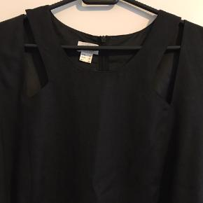 Super flot sort kjole med smukke detaljer på ved skulderne. Mærket er Umlauf & Klein.  Den er af 55% hør og 48 % polyester. Er helfiret