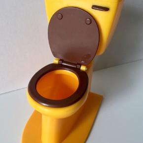 Sælger fint gult/brunt dukke toilet til dukken Sindy. Det er fra 1970'erne. Fin stand uden skader etc. Både bræt og sæde kan vippes op/ned.  Kan bruges til dukker som Barbie, Sindy, Daisy etc.  Højde 14 cm.  Sender gerne mod betaling.