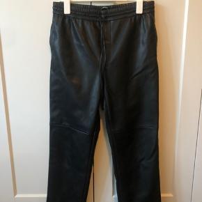 Gina Tricot jogging-lignende bukser i faux læder. Sidder flot og kan snøres lidt til i livet. Brugt 2 gange, ingen brugsspor.