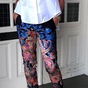Pragtfulde paisleyprintede bukser fra Gustav, fremstillet i det lækreste elastiske polyesterkvalitet i blå, orange og creme nuancer. Velsiddende og behagelig model med bred elastiktalje, stiklommer i siderne, paspolerede baglommer, smalle ben og slidser ved anklerne. str. 38  Almindelig benlængde/benlængde 0.    Materiale: 87% polyester og 13% elastan. Har en ny Mos Mosh skjorte i str M til salg som passer perfekt til bukserne 🌸💕
