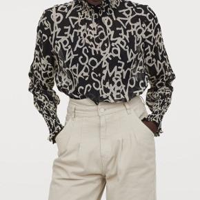 Crinkled bluse i tynd chiffon med trykt mønster. Blusen har smocksyet opadstående krave samt lange ærme med smock forneden.   • Str M / 38 • 100% polyester  • Ny pris 349,- • Beige/ Sort print  • Blusen er kun prøvet på - aldrig taget i brug