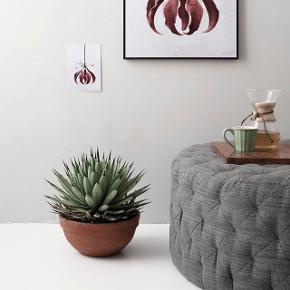 Stor, rund puf med mange knapsyninger, som giver et feminint og eksklusivt udtryk. Puffen kan både benyttes som skammel, ekstra siddeplads eller sofabord og tilføjer et strejf af klassisk elegance til ethvert rum