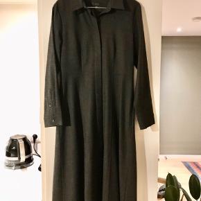 Fin figursyet kjole i glat uld fra Cos.  Kjolen har skjulte knapper hele vejen ned foran og går en smule ud fra taljen og ned, dog uden at være A-formet.  Farven er mørk koksgrå.  Kjolen er brugt 2-3 gange og sælges, fordi jeg ikke får den brugt..