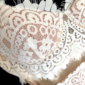 Fin gulvlangkjole med slids, flotte blondedetaljer omkring overdelen og en mesh detalje under brystet. Skålen passer til en B-lille C.