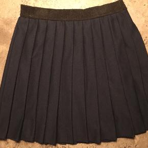 Pliseret nederdel i blå med sort elastikkant. Brugt men i fin stand.