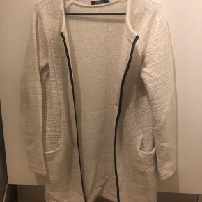 """Str.: 36.  Lys beige/hvid mellemlang cardigan (tyk i materialet). Har sorte """"læder"""" detaljer. Ingen misfarvninger."""