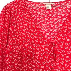 Flot rød bluse med lille lynlås i siden og to bindesløjfer foran. Str. 40, men er nærmere en str. 38.  Kan afhentes i København eller køber betaler fragt.