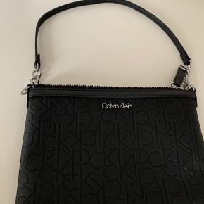 Sød lille sort taske fra Calvin Klein. Den er ikke i rigtig skind.  Længde 24 cm  Brede 16 cm  Remmen er 50 cm.  Der er flere kommer inde i tasken og en lynlås lomme