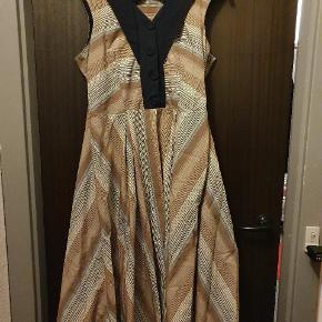 Smuk 50'er inspireret kjole fra svenske Miss Candyfloss. Kjolen lukkes ud over med knapper med en lynlås i siden. Der medfølger et marineblåt bælte til taljen.  Obs. Kjolen egner sig bedst til kvinder med en gennemsnitlig til mindre barm. Bruger man mere end en D-skål(som mig), vil den være meget stram omkring brystet