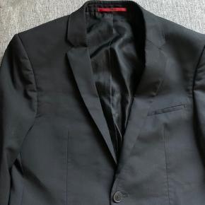 Sælger et Hugo Boss jakkesæt med skjorte også. Det har været brugt 3 gange til julefrokoster og nytår sidste år, og ellers ikke været brugt, da jeg er vokset ud af det.   Bukserne er størrelse UK46 og har haft en lille skramme fra en af julefrokosterne, som er blevet lappet. Kan ses på andensidste billede. Ellers fejler de intet.  Blazeren er størrelse UK46 også, og har en lille rift indeni ved lommen som ses på sidste billede, fejler ellers intet heller.   Skjorten er også Hugo, og er størrelse 38 og fejler intet.