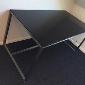 Sort højglans skrivebord med stel af børstet stål.  Lidt ridser i glasset, men ikke noget der har nogen særlig betydning  Dybde 80 cm  Højde 74 cm  Bredde 150 cm