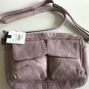 DEPECHE crossbody taske Farve: lys lilla Højde, 19 cm Bredde, 29 cm Dybde, 8 cm Aldrig brugt og stadig med tag. Oprindelig købspris: 1000 Sælges for 400 kr Bytter ikke
