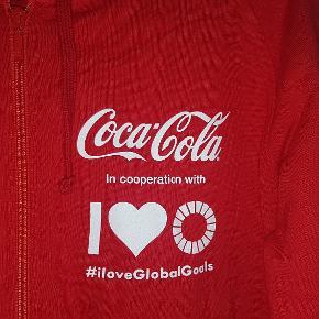 Aldrig brugt! Mærke: Neutral - Certified Responsibility Unisex. Mens size S. Lang hættetrøje med lynlås og lomme på maven.  Klassisk Coca Cola-rød hoodie i 100% økologisk fairtrade bomuld med tryk på for- og bagside samt ekstremt blød inderside.  #iloveGlobalGoals in cooperation with Coca Cola.   Elsker du de globale målsætninger OG Coca Cola? Så er det her hættetrøjen lige for dig. Hvis du på den anden side bare er på udkig efter en fuldstændig ubrugt rød hættetrøje i økologisk bomuld er dette også trøjen for dig.